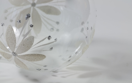 A clear glass Christmas ball decorated with white glittered poinsettia flowers