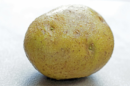 結露で覆われて皮が付いたままのジャガイモの写真