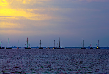 A photograph of sailboats anchored in the bay for the evening