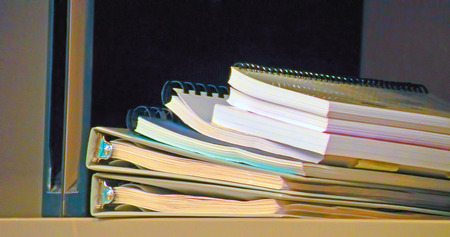 A photograph of a stack of binders and notebooks
