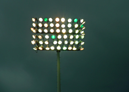 A photograph of a bank of stadium lights against a dark cloudy sky Stock Photo