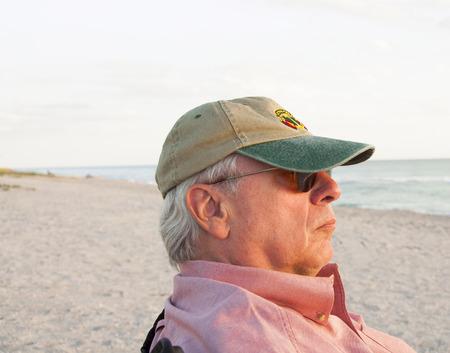 A photograph of man sitting on a beach watching a sunset
