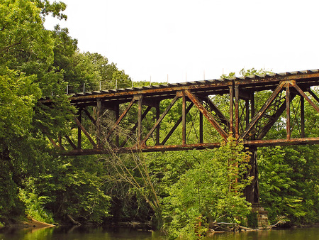 A photograph of an old railroad trestle spanning a shallow river