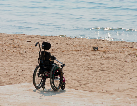 A photograph of an empty wheelchair sitting on a beach