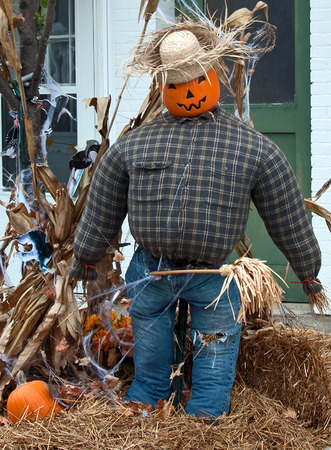 A scarecrow made from a pumpkin, flannel shirt, jeans, and a straw hat sitting on a bale of hay Stock Photo