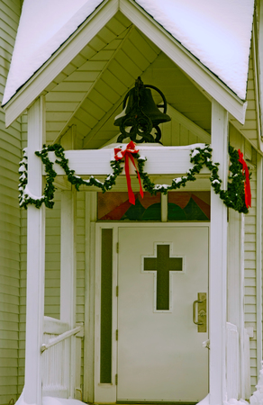 A photo of a dormered entrance to a small neighborhood church decorated for Christmas under a blanket of snow