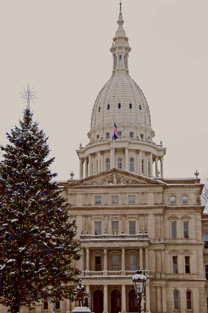 A photo of the State of Michigan Capitol Building with a Christmas tree in the foreground