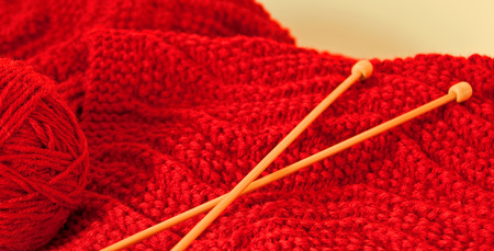 A photo of a hand-knitted red scarf with yarn and knitting needles