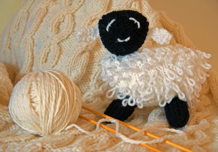 A photo of a hand-knitted, white, baby blanket along with a hand-knitted curly lamb