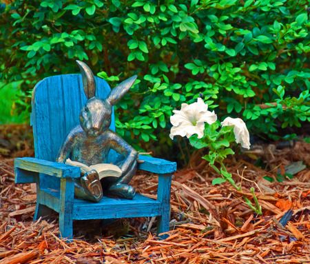 A photo of a garden ornament sitting in a mulched flowerbed - a rabbit reading a book in an Adirondack chair