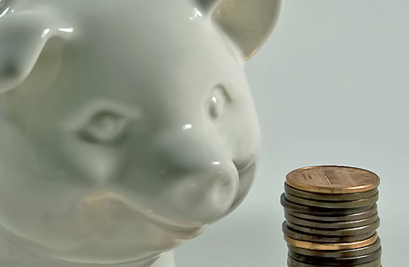 Close up photograph of a white ceramic piggy banks and a stack of pennies