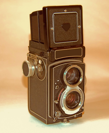 A photo of a German-made vintage camer on a shadowy background with the viewfinder extended