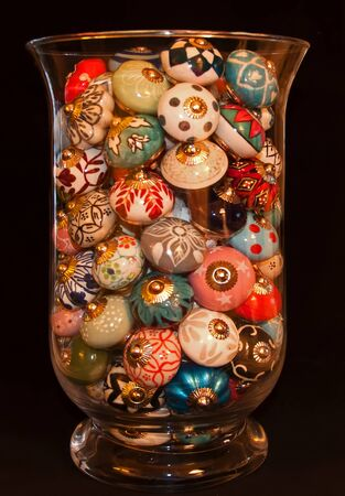A glass container filled with painted drawer pulls in various colors and designs.