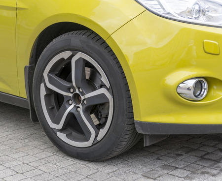 alloy: Yellow car closeup front wheel with light alloy rim