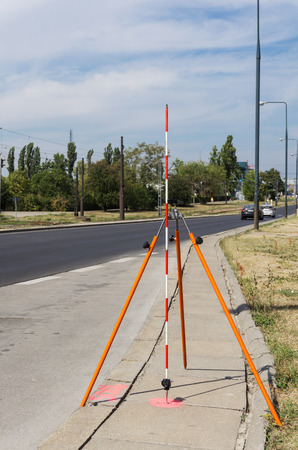 tripod mounted: Offset rod mounted on a tripod placed near the road, pink tag on a pavement Stock Photo
