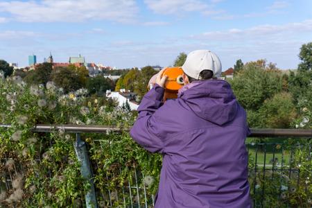コインを探してキャップの女の子は、旧市街の景色は、ポーランドのワルシャワで双眼鏡を運営しています。リアビュー。水平方向の画像