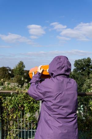 コインを通して見るフード付けコートの少女は、町のパノラマ、ワルシャワ、ポーランドで双眼鏡を運営しています。リアビュー。垂直方向の画像