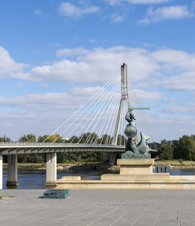 gunmetal: Warsaw mermaid Mermaid statue with holy cross Swietokrzyski Bridge in background. Symbolemblem of Warsaw. Statue made of gunmetal, was erected in April 1939. Stock Photo