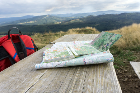 Wooden bench with hiking maps and a backpack. Mountain landscape in background, nobody.Silesian beskids, Poland.
