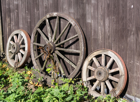 rims: Three old wagon wheels with metal rims leaning against a wall of wooden planks Stock Photo