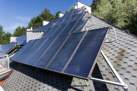 solar heating: Hot water solar heating system - Solar panels on the roof - green energy, renevable energy, alternative energy - horizontal  image - nobody