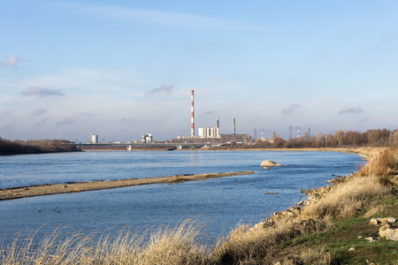 greenhouse effect: The power plant, heating plant on the banks of the river. Industrial landscape. Illustration of global warming or greenhouse effect. Stock Photo