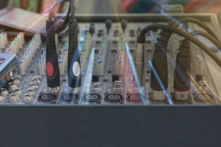 jacks: Audio jacks and wires connected to audio mixer, music dj equipment. Concert or party with colored lights.