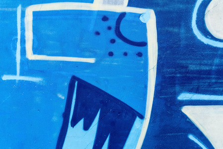 grafiti: Detail of a graffiti art on a wall. Wall painted in different colors. Abstract blue background.