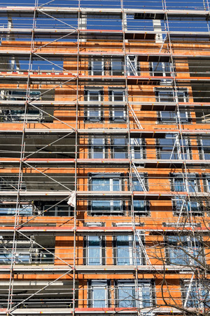 scaffolds: Building construction site with scaffolding. Walls from red bricks. Vertical image. Nobody