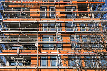 Building construction site with scaffolding. Walls from red bricks.