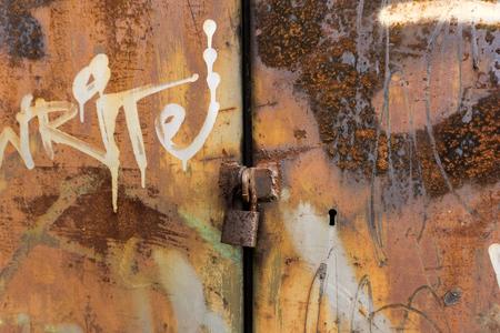 metal grunge: Rusty metal door locked with padlock and keyhole