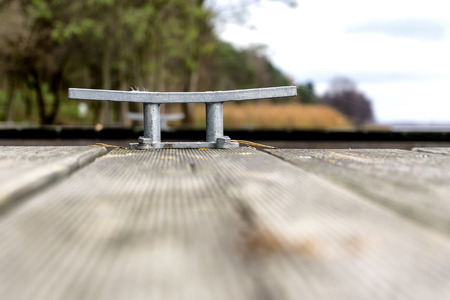 cleat: Wooden pier with cleat. Nobody. Selective focus Stock Photo