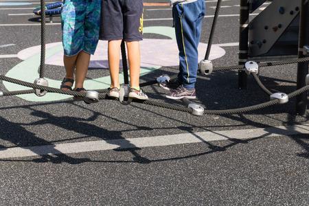 sandalias: Tres niños que juegan en la red de la cuerda en el parque en un día soleado de verano