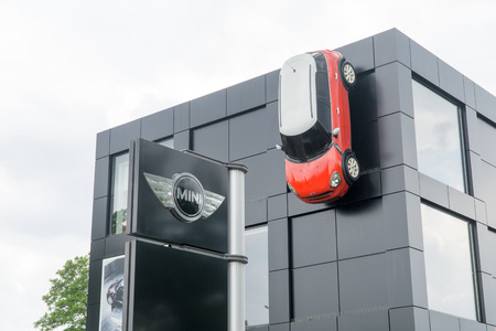 cooper: WARSAW, POLAND, May 21, 2016: Red Mini Cooper 5 with white roof  mounted on the wall of the building a car showroom. MINI Cooper is a brand of car made by BMW.