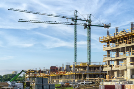 property development: The construction site. Construction of the new residential building. Construction cranes.
