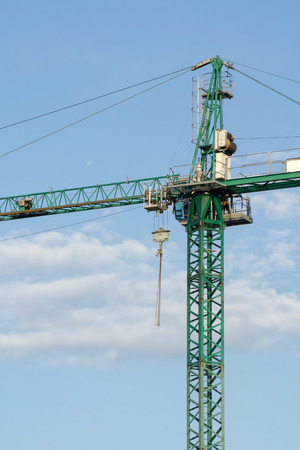 elevator operator: Green tower crane closeup. Crane operator leaves his cabin. Blue sky with white clouds in background.