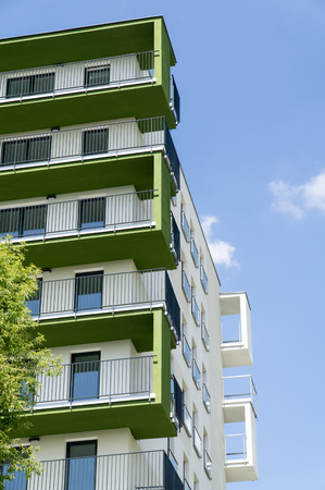 residential: Modern residential building facade with green balconies. Bottom view