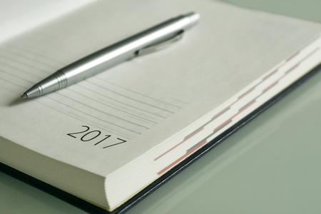ballpen: New Year 2017 office organizer calendar and sliver ballpen. Selective focus