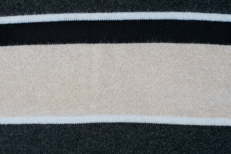 knitwear: Knitwear striped in grey, black, beige, white. Textured background. Stock Photo