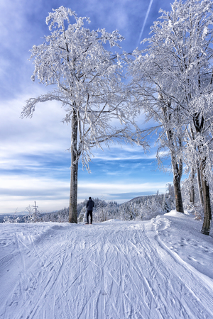 Single tourist, cross country skier is resting  on the top of the hill, under frosted tree, beech. Admires snow covered mountains. Winter mountains landscape, Slovakia, Europe. Stock Photo