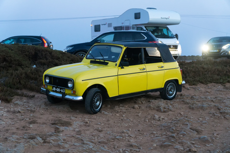 CAPE ST. VINCENT, PORTUGAL - SEPTEMBER 5, 2018: Yellow Renault 4 car oldtimer convertible parked at stony parking by the sea at sunset. Редакционное