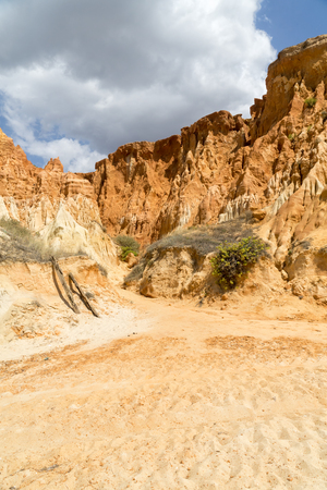 High cliffs along Falesia Beach and The Atlantic Ocean in Albufeira, Algarve, Portugal. Sunny summer day, blue sky with stormy clouds.