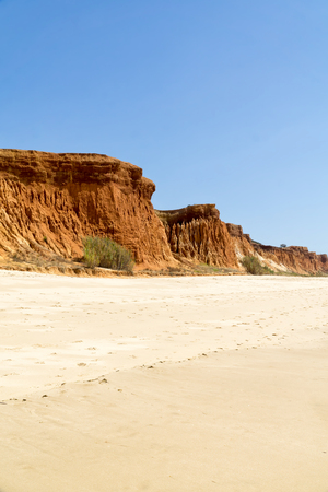 High cliffs along Falesia Beach and The Atlantic Ocean in Albufeira, Algarve, Portugal. Sunny summer day, blue sky. Фото со стока