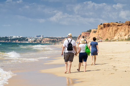 Senior couple walking on the beach on the summer sunny day