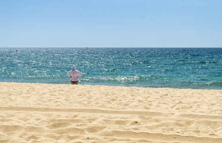 Mature woman in white shirt and white hat is standing on the beach and watching the sea in sunny summer day.