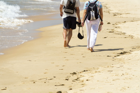 Couple walking on the beach in the summer sunny day.