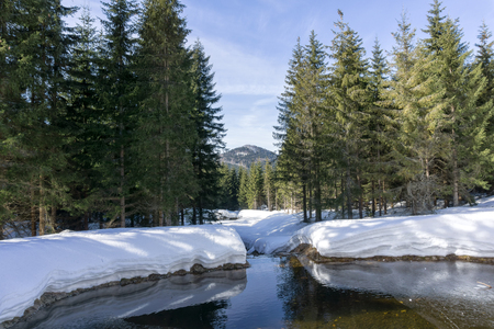 Winter mountain landscape with stream surroundings of Jakuszyce, Poland. View on Bukovec  peak in Jizera Mountains.