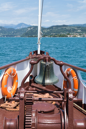 Bell on bow of ship on Garda Lake in sunny summer day, Italy, Europe. Concept of summer leisure.
