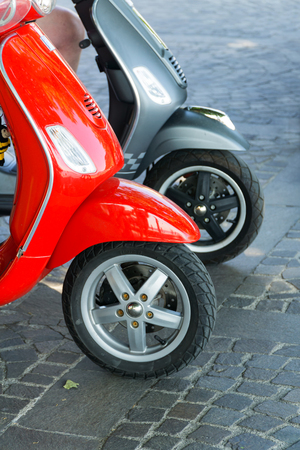 Two parked red and gray scooters on a cobblestone street, detailed front view, selective focus. The concept of ecological urban transport.