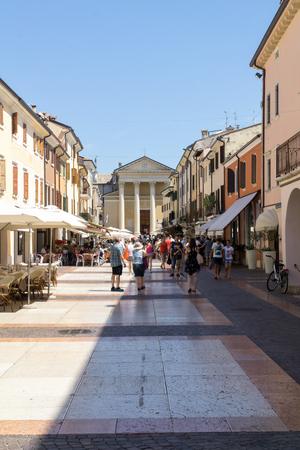BARDOLINO, VENETO REGION, ITALY - AUGUST 7, 2017: People on main street of village of Bardolino in front of Parish Church.